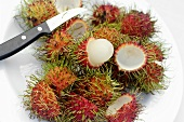 Whole and peeled rambutans on a plate with knife