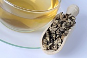 Cup of tea with dried black cohosh root in scoop