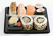 Assorted sushi in a plastic box with soy sauce & ginger