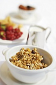Muesli, a small jug of milk and fresh fruit