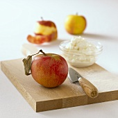 Apple, a dish of quark and a knife on chopping board