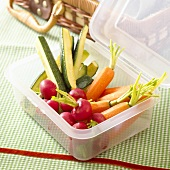 Carrots, radishes and courgettes in a plastic box