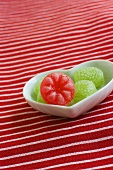Green sweets and one red sweet in a heart-shaped dish
