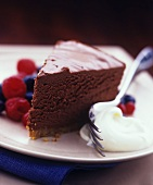 A piece of chocolate cake with whipped cream and berries