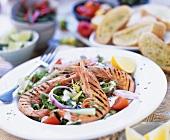 Grilled prawns on summer salad with herb baguette