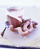 A glass of hot chocolate with curly doughnuts