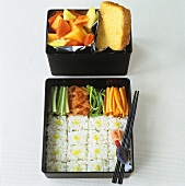 Sushi, vegetables, fruit salad and cake in bento boxes