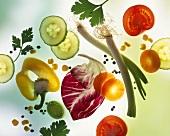 Vegetables, herbs, salad leaves & seasonings on a sheet of glass
