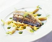 Fried sea bass on vegetables with pesto