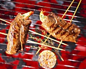 Beef and prawn skewers on a barbecue