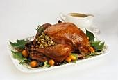 Stuffed turkey on a platter with gravy boat