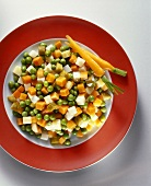 A plate of buttered vegetables with gherkins