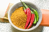 Curry powder and chili peppers in bowl