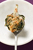 Stuffed artichoke with gratin topping on spoon
