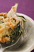 Stuffed artichoke with gratin topping on spoon, close-up
