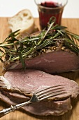 Roast lamb with rosemary, slices carved, white bread, red wine