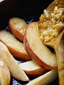 Fried apple wedges in frying pan