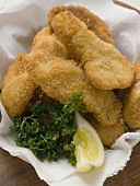 Fish nuggets with lemon wedge and parsley