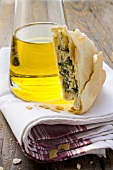 A piece of spinach and ricotta pie beside bottle of olive oil