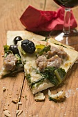 Two slices of pizza with tuna, chard and olives