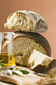 Rustic bread, two loaves with pieces cut off, olive oil, salt