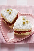 Heart-shaped cakes with jam, icing sugar, daisies