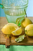 Fresh lemons with leaves in front of water jug