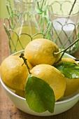 Fresh lemons with leaves in bowl, lemon juice, sugar