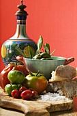 Fresh tomatoes, olives, bread, salt and ceramic jug