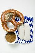 Two Weisswurst in packaging, pretzel & mustard