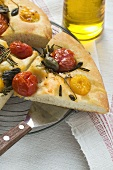 Three slices of pizza with cherry tomatoes, capers & rosemary
