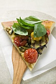Slice of pizza with aubergines, cherry tomatoes & basil