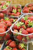 Fresh strawberries in plastic punnets at a market