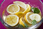 Squeezed lemons in water in glass bowl