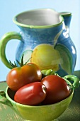 Tomatoes in green bowl in front of ceramic jug
