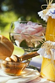 Honey in glass bowl, bread roll, jars of honey