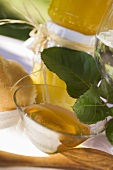Honey in glass bowl in front of jars of honey