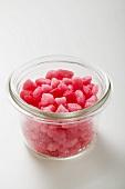 Kleine rosa Zuckerbonbons im Glas