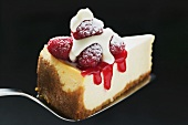 Slice of cheesecake with raspberries, cream, icing sugar on server