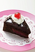 Slice of chocolate cake with cream and cherry on doily