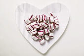 Cherry mint sweets on heart-shaped paper plate