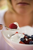 woman eating berry muesli with yoghurt