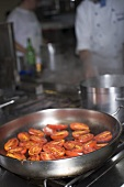 Tomatoes in frying pan on stove, chefs in background