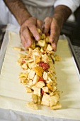 Making fruit strudel: spreading filling on strudel pastry