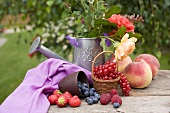 Peaches, berries and summer flowers on table in garden
