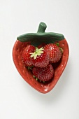Four strawberries in red strawberry-shaped dish