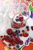 Frische Beeren im Marmeladenglas mit Zucker und Kochlöffel