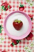 Strawberry in a small dish of sugar