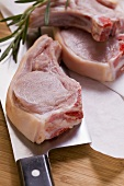 Raw pork chops with meat cleaver and rosemary