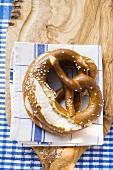 Soft pretzels on tea towel on chopping board